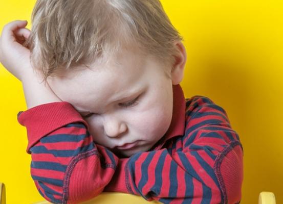 Smutne dziecko na żółtym tle