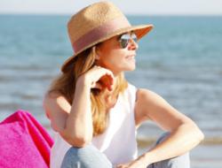 kobieta w kapeluszu siedząca na plaży